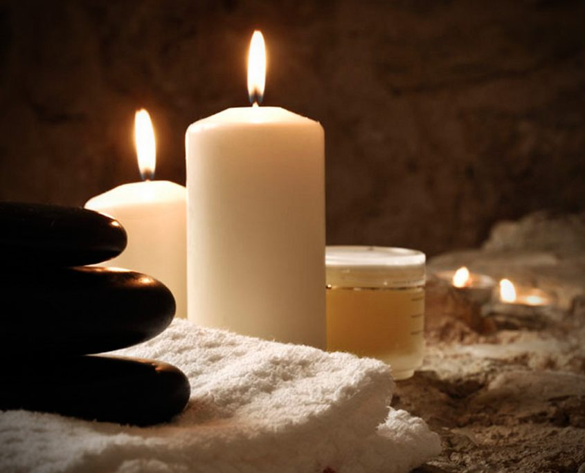 Candles and rocks on sand