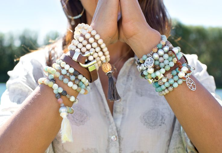 palms touching with multiple bracelets on each arm